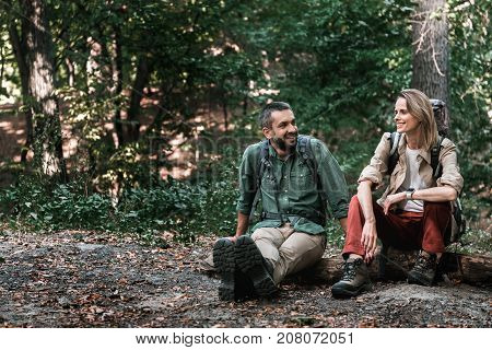 Portrait of happy couple sitting and talking while sitting on pathway with relaxation. They are carrying backpacks and laughing