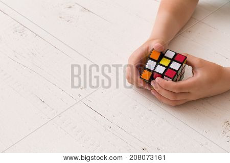 Moscow Russia August 24 2017: Rubik's cube in woman's hands closeup top view white wooden background. Girl holding Rubik's cube and playing with it.