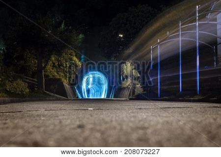 Night scene with a blue lightened tunnel and a abstract silhouette with a light trail, Japan