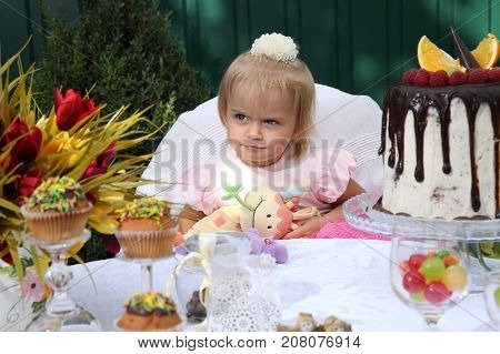 Girl birthday. A little white-haired girl of two years is trying a birthday cake. Little girl celebrating second birthday.