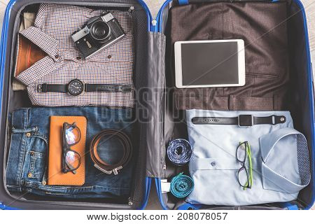 Shirts near trousers in open suitcase. Tablet and other accessories on clothes. Top view close up. Nobody
