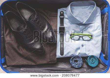 Shirt is near trousers and shoes in open suitcase. Necessary accessories are on wear. Top view. Close up