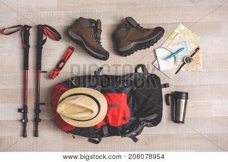 Big backpack is near sticks for Nordic walking and maps on floor. Boots nearby thermos flack. Top view close up. Nobody