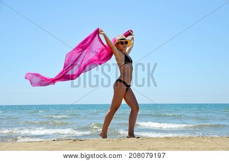 Beautiful caucasian girl with scarf on the Beach.Summer vacation by the sea.