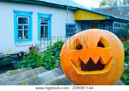 orange pumpking with cut face is ready for Halloween on the rural house background