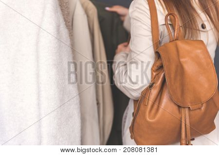 Girl is standing near overcoats and looking through it. She carrying brown leather rucksack. Focus on backpack. Copy space on left side