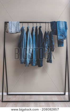 Various blue jean shirts and trousers are at hangers in wardrobe. Copy space. Nobody
