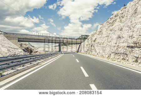 Bridge over a highway on a background of mountains and blue sky.