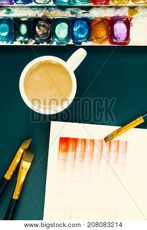 Artist work place. Coffee break on the lesson of watercolor painting. Paper palette acrylic paintbrush and a cup of coffee. The Lesson for the beginners painting tools. Watercolor painting process