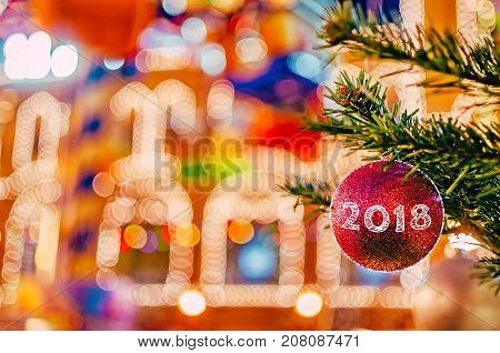 Bright Christmas and New Year background. Christmas and New Year decorations background. Red christmas ball on fir branch with text 2018.