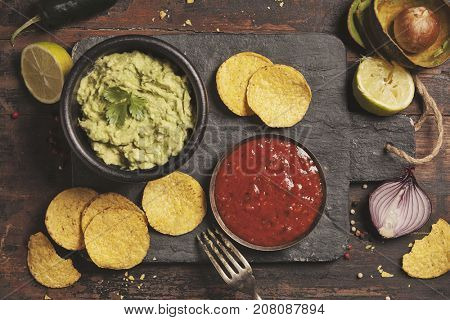 Mexican nachos chips with homemade fresh guacamole sauce and salsa over old background. Top view. Mexican food concept