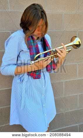 Female jazz trumpet player with her horn outside.