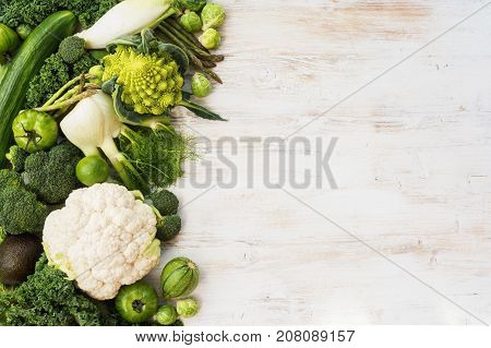 Green vegetables and fruits on the white wooden table, copy space for text on the left, horizontal, top view, selective focus