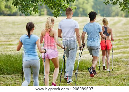 Young people in hiking club nordic walking in the nature