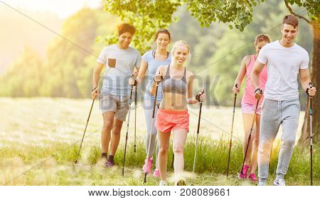 Group in summer nordic walking in their fitness class