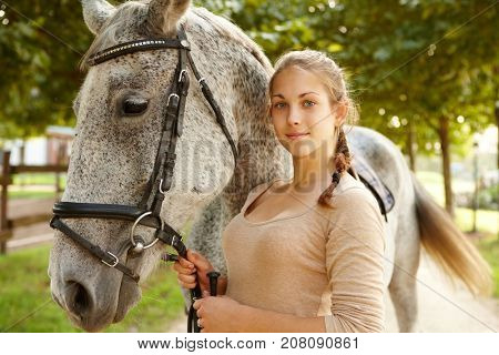 Outdoor photo of young female with her horse, smiling, looking at camera.