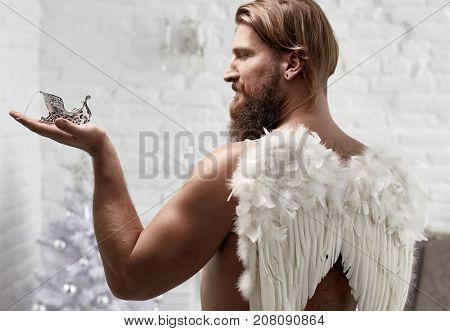 Muscular bearded man wearing wings acting like a Christmas angel.