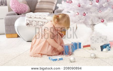 Little girl lost in playing by christmas tree.