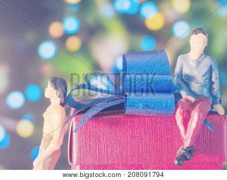 Miniature man and woman with red box in romantic night