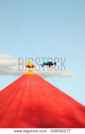 Blue drone flying over red circus tent against a blue sky and white clouds in summer time and shoots a video