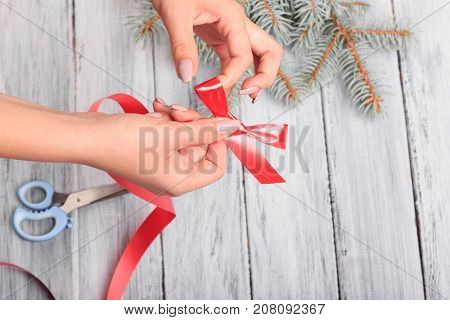Hands with scissors. Red ribbon. Close-up. Next to it is a branch of spruce.