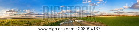 beautiful rural autumn landscape panorama with road field and blue sky with white clouds. panoramic autumn view. sunset over agricultural fields and path