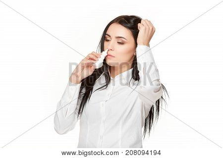 View od sad unhealthy brunette woman with long hair, holding head by hand and drown nasal spray in nose. Home therephy for allergic, infection and flu in autumn season. Woman with virus and symptoms.