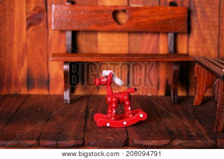 Miniature red rocking horse sitting on front porch in front of wooden bench with heart shaped cut in back.