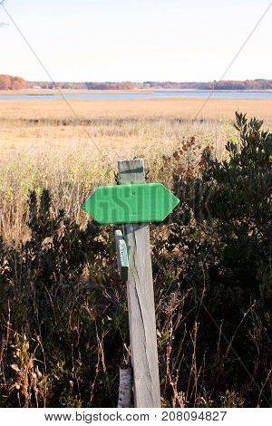 Green trail marker on a wooden post along a walking trail around a salt marsh.