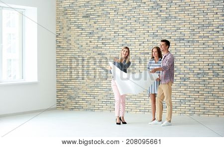 Real estate broker showing customers plan of new flat