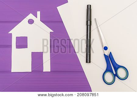 Paper silhouette Paper silhouette of white house, scissors and marker near on a white sheet of paper on purple wooden background. Housing concept