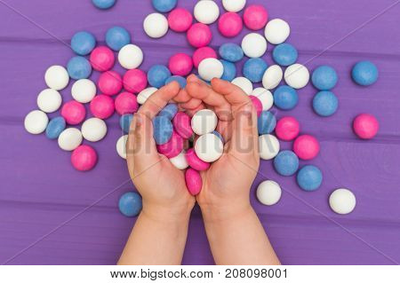 Children's hands holding colored candies above purple wooden board