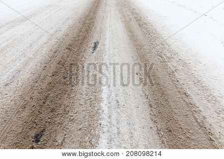 covered with a dirty snow road for the movement of cars. Winter season. The photo is made close-up where the tracks from the transport buses are clearly visible