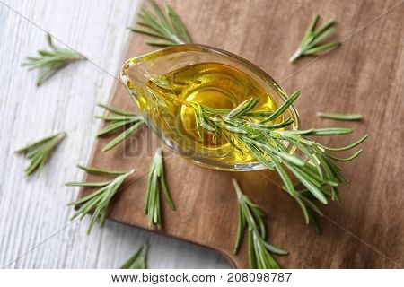 Gravy boat with rosemary oil and herb on wooden board