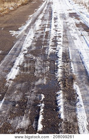 an old asphalt road covered with snow. Winter time of the year, ice lines are visible on the surface. Close-up photo