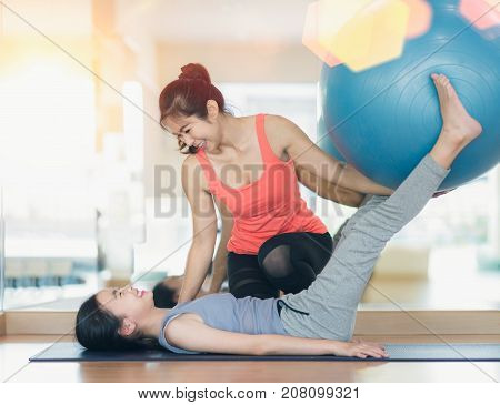 Asian woman fitness coach teach her student for rubber ball exercise in fitness center