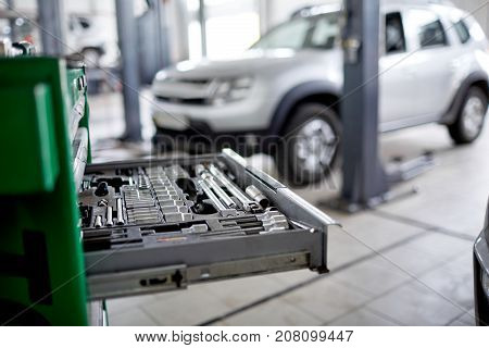 Extended green box with tools in focus on the blurred car background