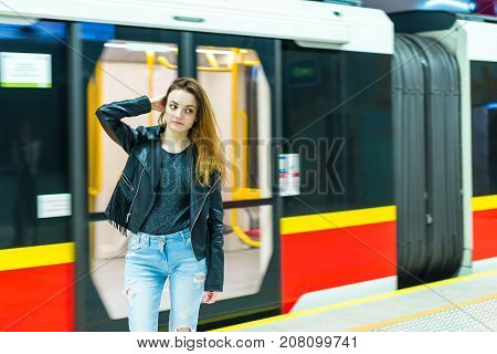 The girl near subway train at the metro station