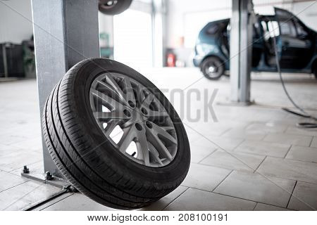 Unscrewed car wheel in white car service room