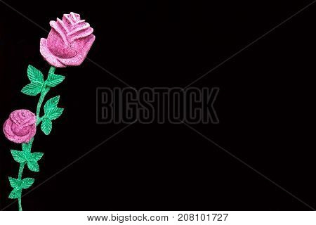 horizontal image of an imitation of a pink coloured rose with green stems placed on one side on a blank black background with lots of room for text. great for greeting cards or advertising.