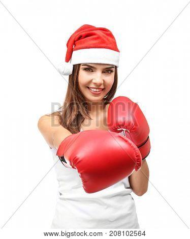 Beautiful young woman in Santa Claus hat and boxing gloves on white background. Boxing Day concept