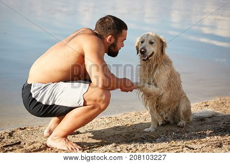 Beautiful golden retriver and owner playing near the river. Doggie gives a paw to owner. Cutie pet and man enjoying life on the fresh air on the water background.