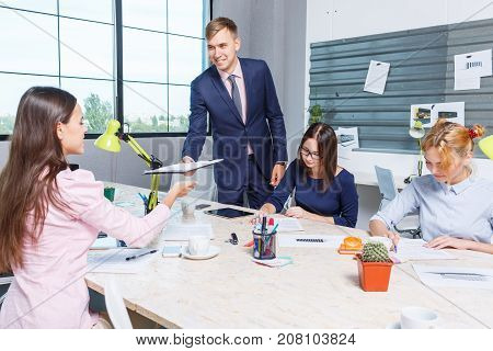 A young, handsome boss passes his documents to his office worker a beautiful girl