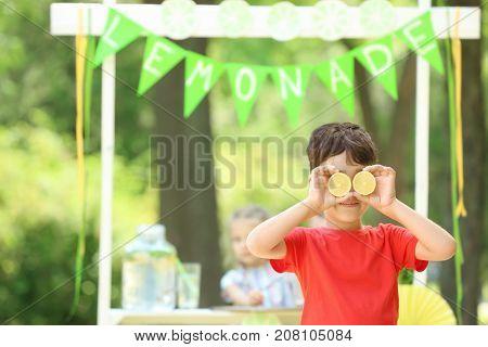 Funny little boy near lemonade stand in park