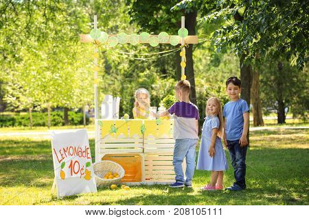Adorable children standing in line for homemade lemonade outdoors