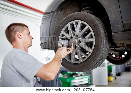 Handsome mechanic in uniform is working in auto service. Car repair and maintenance. Twisting and untwisting bolts on wheel.