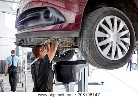 The mechanic works at the bottom of the car, which stands on the lift