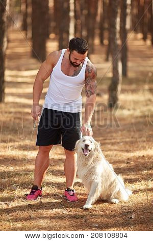 Handsome young man with beard in white T-shirt walking with dog in the forest outdoors on a nature background. Full lenght of man. Nature concept.