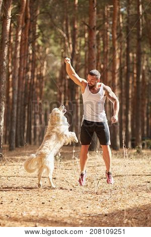 Handsome young man with beard in white T-shirt playing with dog in the forest outdoors on a nature background. Full lenght of man. Nature concept.