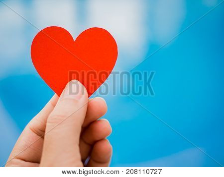 Closeup hand holding red paper heart shape on blue background. Love and Valentine concept.